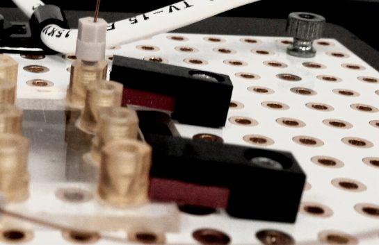 Microfluidic chip clamp secures microfluidic chip to breadboard